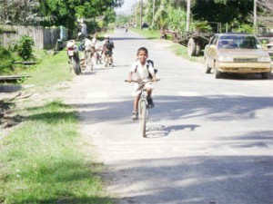 A student of the San Souci Primary School on his way home. Many residents of Wakenaam, including students and workers, use bicycles to move around the island.