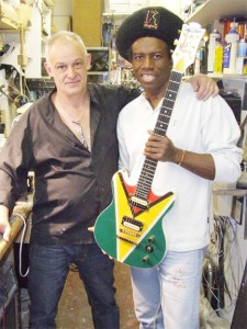 Eddy Grant (right) holds his 'Ringbang Guyana' guitar. At left is the guitar maker, Philippe Dubreville a Frenchman living in England. (Photo courtesy of Eddy Grant)