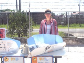 Patricia McArdle of Solar Cookers International stands behind the Cookit solar cooking apparatus.