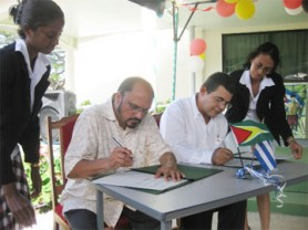 Jorge Rodriguez, Charge D'Affairs, Cuban Embassy and Minister in the Ministry of Health Dr Bheri Ramsarran signing the Guyana-Cuba agreement.