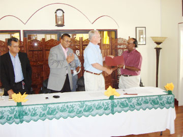 Dr Oudho Homenauth (right) and Howard Stine shake hands on the deal. Also in photo from left are Private Sector Commission Chairman Gerry Gouveia and Agriculture Minister Robert Persaud.  (Ministry of Agriculture photo)