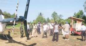 Members of the joint services stand near the GDF helicopter at Abary after the rescue.