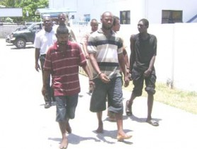 Four of the accused in the kidnapping of Mahaicony rice farmer Parasram Ramnarace and his employee Patrick Skeete, making their way to the Vigilance Magistrate's Court in the company of policemen yesterday. From left (in foreground) are: Michael Payne called Michael Henry, Denswick Booker called `Garry', Rajan Persaud called `One Hand' and Dwaine Johnson called Dwaine King. (Orlando Charles photo)