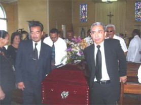 Dr. Raymond Chung (left), bearing the coffin which bore his mother's body, along  with his cousin Wallace Quan (right) and other relative yesterday