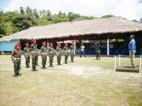 Indigenous members of the Guyana Defence Force last Friday as they prepared to salute Prime Minister Sam Hinds at the Orealla Heritage day celebrations. In the background is the $1.5M benab that was built for the occasion. (Sara Bharrat photo)