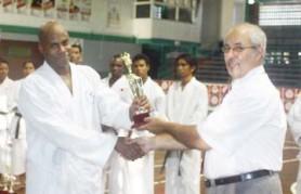 Winner of the Male Over-80kg Kumite Category, Darren Nurse of Guyana Wado-ryu Karate Association receiving his trophy from Amir Khouri.