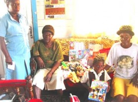 Candacy Britton posing with the items she received in presence of the School's Welfare Officer Gillian Vyphuis (standing at left); her aunt Waveney Pollydore (right) and her great grandmother; Vida Britton.
