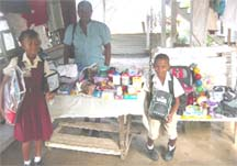 Candacy (left) and Eon display the items they received from Deborah Leow, while School's Welfare Officer Gillian Vyphuis looks on.