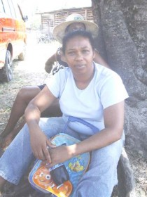 Sandra Beharry taking refuge under a tree while fire ravaged her home at Rose Hall yesterday.