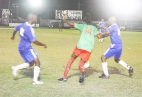 A GDF player at centre fights to maintain possession against two Milerock defenders. (Orlando Charles Photo)