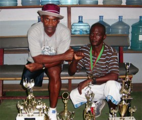 Champion walkers! National race walk champion Rudolph Mitchell (right) poses with his trophies and potential manager William 'The Conqueror' France at the Stabroek News building yesterday.