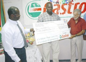 OILING UP! Guyoil's Chairman of the Board of Directors Dr. Bud Mangal (right) hands over his company's cheque of $200,000 to president of the GABBFF Frank Tucker while 2009 Mr. Guyana Oswin Jones (centre) looks on. (Orlando Charles photo)