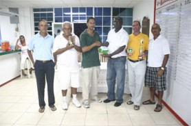 Stabroek News' Sports Editor Donald Duff, third from right, hands over the first place trophy to Andre Cummings winner of the inaugural de Caires/Mackie Memorial golf tournament which took place yesterday at the Lusignan Golf Club course. Others in photo are from left, Ronald Bulkan, secretary of the LGC, Dr Cecil Ramsingh, second place finisher, William Walker who placed third and Club Captain Jerome Khan.(Orlando Charles photo.)