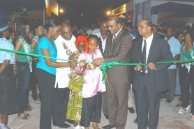 President Bharrat Jagdeo (second from right) assists two girls in cutting the ribbon last evening following the Opening Ceremony of GuyExpo. Looking on are co-Chairmen of the event Derrick Cummings (second from left) and Trade and Commerce Minister Manniram Prashad (right).  (Photo by Jules Gibson)
