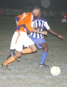 Fruta Conquerors' Trevon Lycott (left) moves down the flank while being marked closely by a GFC defender. (Orlando Charles photo)
