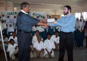Shaikah Moeen Ulhack (right), receiving the checque from Kayum Khan. In background, students of the CIOG look on.
