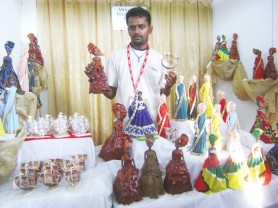 "Man and his dolls: While many might think that dressing dolls is only pursued during the childhood years, Mohamed Kahmar has taken a different view and does this to earn his living. It is his main source of income, he said. The Number Two Village, West Coast Berbice resident (and his dolls) were participating in GuyExpo 2009 for the first time and were one of the attractions yesterday. Kahmar said that thus far, the experience was ""okay."" The man has been dressing dolls since 1996 and says that he purchases the dolls and dresses them in his creations. He also makes ceramic dolls and little wooden ships. According to Kahmar, people are interested and are buying. Especially popular, he said, are the dolls dressed in banana leaves. Kahmar operates out of his home and many of his dolls are made to order. (Photo by Gaulbert Sutherland)"