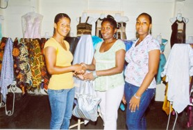 Gileon James of Wilo's Bridal and Fabric Boutique presents Guyana world champion boxer Shondell Alfred her gifts in recognition of her winning a world title. Also in the photo is an employee at the store.