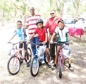 Nicholas Nandan, Deeraj Garbaran and Christopher Griffith pose with National Cycling Coach Hassan Mohammed and their new bikes. (Aubrey Crawford photo)