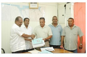 Minister Kellawan Lall (left) handing over the contract document to Mahadeo Umraow of Eagle Transportation and General Construction while other contractors look on. Permanent Secretary of the Ministry Sewchan is second from left.