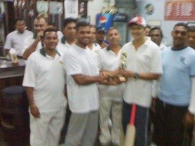 Floodlights XI Skipper Kemal Seebaran receives the winning trophy from Managing Director of Khan's Trading Enterprises and Auto Sales after beating the Pritipaul Singh Investment team.
