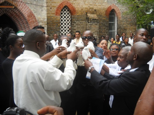 Relatives and close associates of Winston Murray about to release doves following the funeral service in Leguan today.