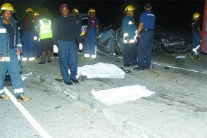 Fire officers stand around the bodies of two of the accident victims, who were killed on Friday evening on the Churchill-Roosevelt Highway in Arouca. (Trinidad Guardian photo)