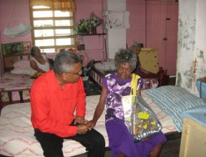 Minister Manzoor Nadir greets the oldest resident of the Palms, Ruby Wilkinson, who is 101 years old. (GINA photo)