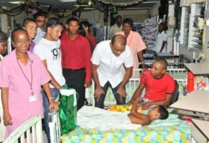 President Bharrat Jagdeo wishing a child at the paediatric unit of the Georgetown Public Hospital Corporation a merry Christmas in the presence of West Indies batsmen Shivnarine Chanderpaul and Ramnaresh Sarwan. (GINA photo)
