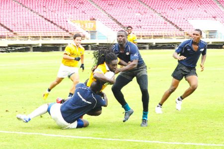 National rugby Sevens Coach/player, Theodore Henry (with ball) is brought down during one of the national rugby Sevens squad's trial games yesterday at the Providence National Stadium (Orlando Charles photo)