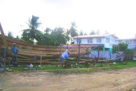 Here Sookdeo double checks the measurement on a boat that is being built at his Pump Road, Mon Repos location.
