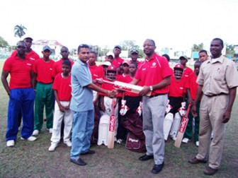 Digicel's CEO Gregory Dean presents Guyana Cricket Board (GCB) General Secretary Anand Senasie with bats for the programme as young cricketers look on. Also in the photo are Reon King (right) and coach Garvin Nedd.