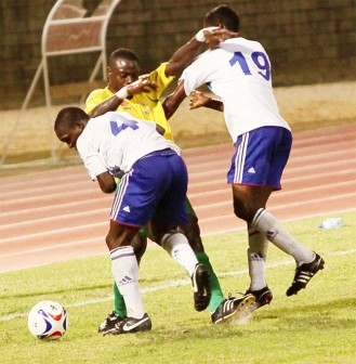 Action in the match between Guyana's Milerock and Trinidad's Defence Force Friday night in the twin island republic.