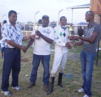 Champion jockey Colin Ross, second right, receives his prize from Partrick Davis of the Guyana Horse Racing Association (GHRA) while champion trainer R. Ramroop (centre) of the Jumbo Jet Stables receives his accolade from Lionel Moonsammy at left of the PMTC.