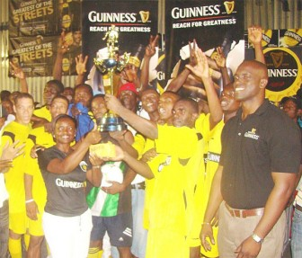 Linden Branch Manager Shondell Easton presents the winning prize to the Eagles team while Guinness Brand Manager Lee Baptiste (right) looks on.