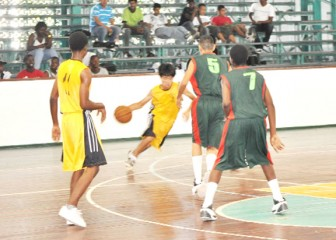 QC's Kitfai Sue (with ball in hand) goes into his dribble as he drives the lane against the Bishops' High defence in the Division Two matchup.