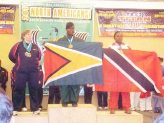 Dawn Barker donned the Golden Arrowhead in Miami yesterday after winning gold and setting a new record. Flanking her are USA champion Malinda Baum (left) and Trinidadian Cheryl Abraham who got second and third respectively.