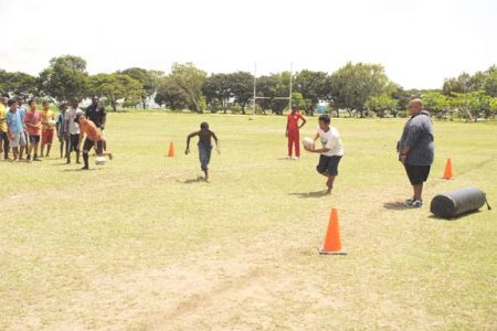 Troy Yhip (extreme right) looks on as some of the students go through some drills yesterday at the School's Rugby Summer Programme held at the National Park rugby field.