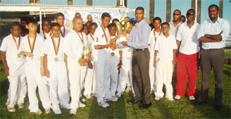 Tropical Mist Brand Manager Errol Nelson presents the captain  of the DCC team Shemar De Souza  with the winning trophy while members of the team look on.