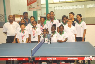 The proud Guyanese delegation displayed their third place trophy and medals yesterday at the Cliff Anderson Sports Hall. (Aubrey Crawford photo)