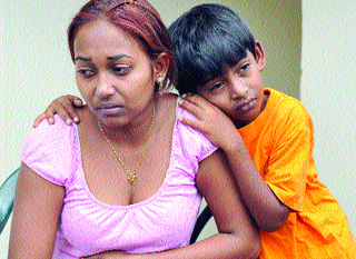 Amanda Ramnath and her brother, Justin, weep yesterday after Friday night's fire at Fyzabad in which their mother, Nowmattie, died. (Trinidad Express photo)