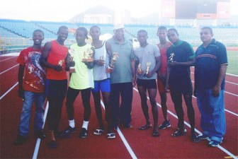 An eight-member squad from the Enmore Athletic Club and their coach John Martin (extreme right) display the trophies won at the Morvant Jets game hosted a the Hasley Crawford Stadium in Trinidad and Tobago.