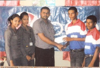 Vice-Captain of the Pepsi Under-19 team Loyydel Lewis accepts the sponsorship cheque from DDL Branch Manager, Albert Budhoo, in the presence of company representatives and team members.