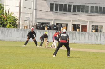 Police Sports Club batsman plays a shot as DCC's wicketkeeper Derwin Christian and Dennis Squires at first slip look  on. (Aubrey Crawford photo)