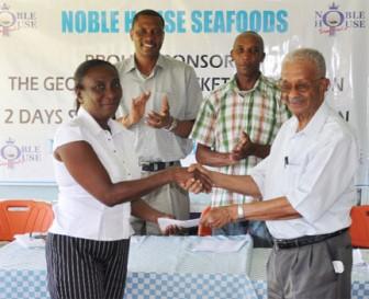 Georgetown Cricket Association (GCA) secretary Deborah Mc Nichol receives tournament sponsorship check from Noble House Seafoods representative Piercy Corlette