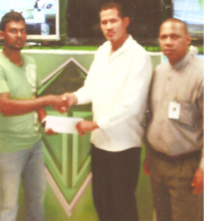 Gizmos & Gadgets Marketing  Manager Mr. Trevor Rose hands over the cheque to RHTYSC cricketer Rajiv Ivan.
