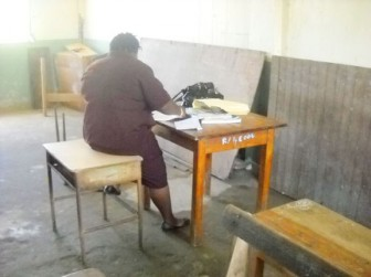 Having no chair a teacher sits on a desk to mark the daily register at the Golden Grove Secondary School on the first day of the term. (SN file photo)
