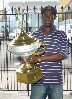Organising Secretary of the Guyana National Dominoes Association (GNDA) Mark 'Jumbie' Wiltshire displays the first place trophy.