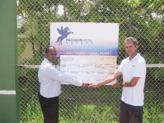 Arnold Sukhraj (left) Facilities Manager of Pegasus hands over the sponsorship cheque to tournament director Andre Lopes.