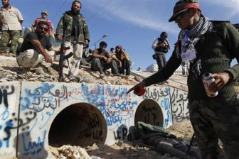 An anti-Gaddafi fighter points at the drain where Muammar Gaddafi was hiding before he was captured in Sirte yesterday. REUTERS/Thaier al-Sudani